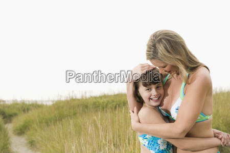 portrait of mother hugging daughter on
