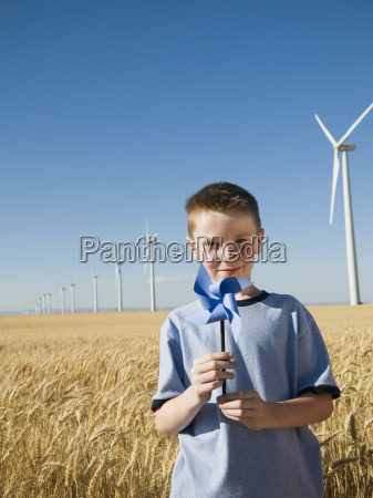 junge haelt nadelrad auf windpark
