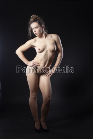 naked woman is standing on black