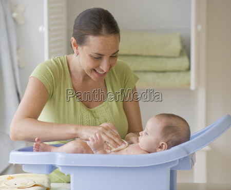 mother bathing baby son in baby