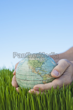 male hands holding globe over grass