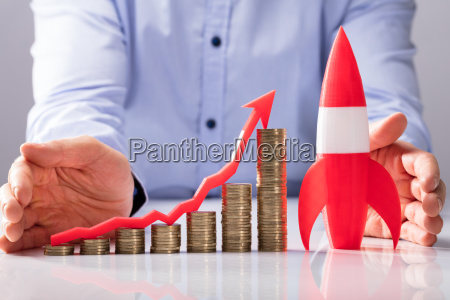 businessperson protecting rocket stacked coins and