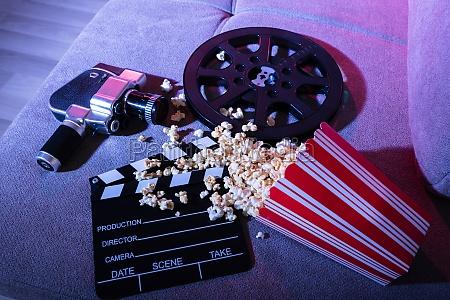 verschuettetes popcorn mit clapperboard und film