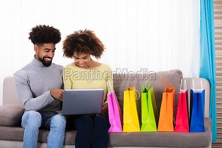 junge paare die online auf laptop