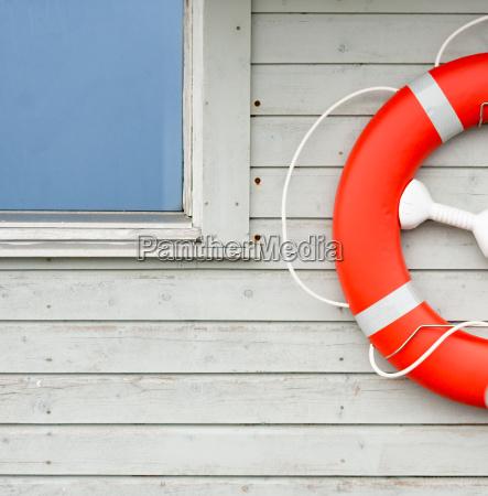orange rettungsring auf weisser wand im