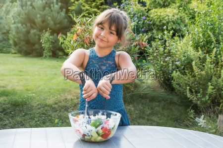little girl is cooking salad in