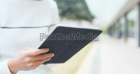 frau die mit digitalem tablet computer