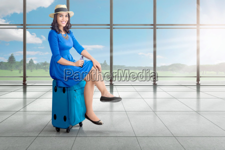 beautiful asian woman sitting on suitcase