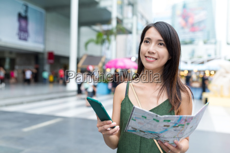 tourist using cellphone and holding city