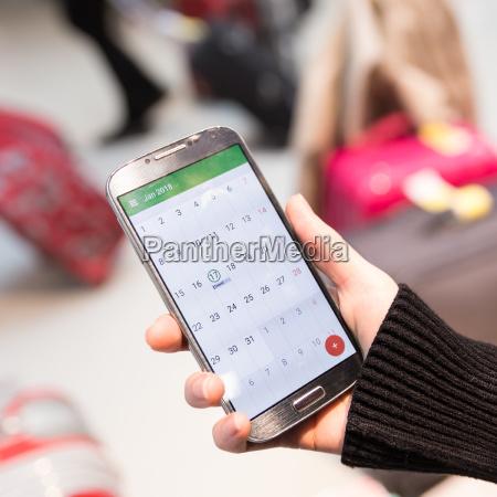 woman checking calendar information on mobile