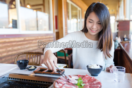 woman enjoy barbecue in japanese restaurant