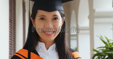 asian woman wearing graduation gown in