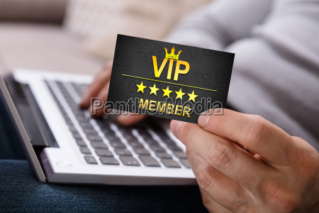 person using laptop holding vip member
