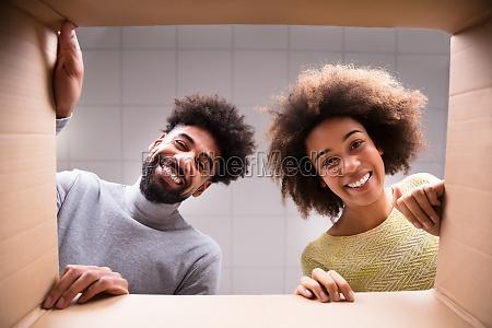 happy couple looking inside cardboard box