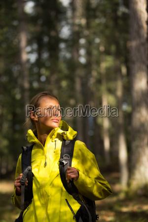 pretty young female hiker walking through