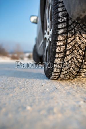auto mit winterreifen auf rutschigem schneebedeckter