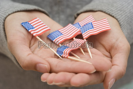 hands holding small us flags