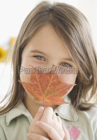 girl holding autumn leaf in front