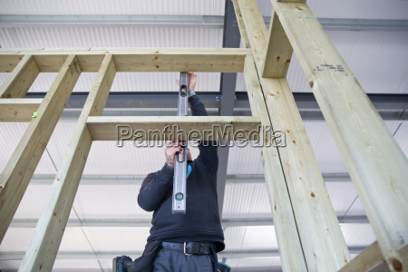 carpenter using spirit level to check