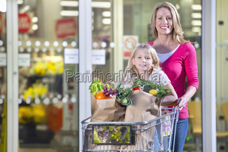 mother daughter shopping groceries supermarket trolley