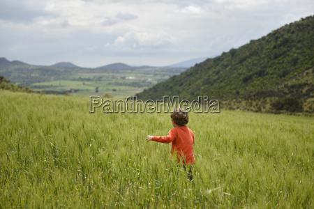 toddler running through wheat field tepeapulco