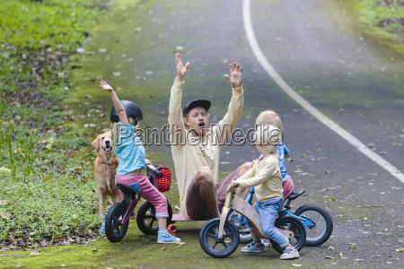 father with three children in park