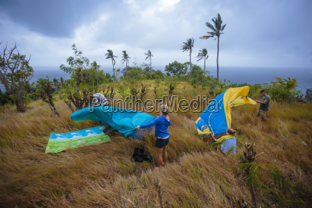 people setting up tent in meadow