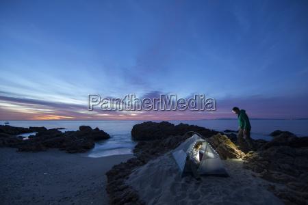 couple tent camping along the shoreline