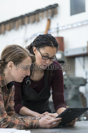 two women standing at workbench in