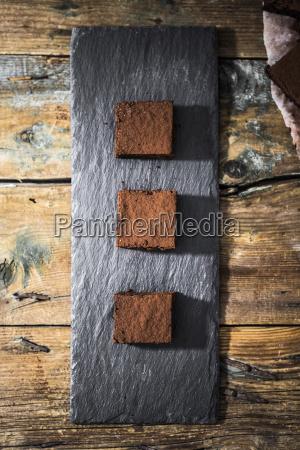 drei hausgemachte brownies auf schiefer