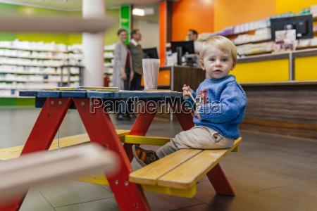 kleiner junge sitzt auf bank in