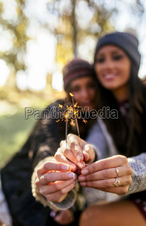 hands of two women holding sparklers