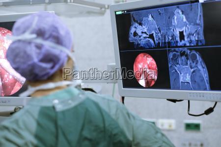 neurosurgeon in scrubs looking at monitor