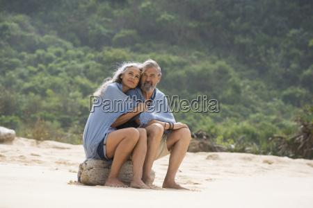 senior couple sitting on the beach