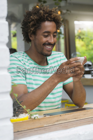 smiling man checking his smartphone at