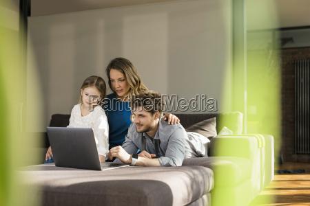 familie mit laptop auf sofa zu
