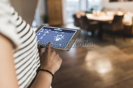 woman using tablet with smart home