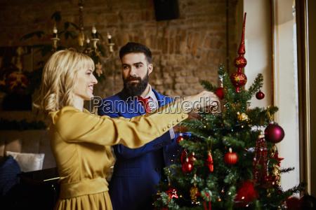elegantes paar schmueckt weihnachtsbaum
