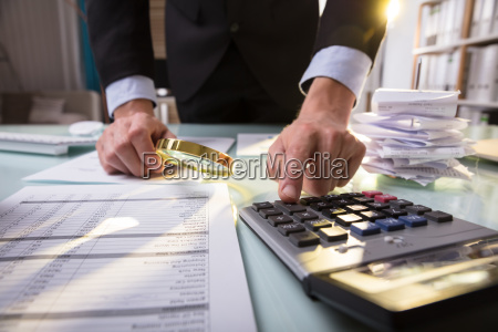 businessperson looking at document through magnifying