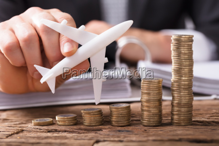 businessperson flying aeroplane over stacked coins