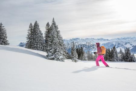 huebsche junge frau schneeschuhwandern in hohen