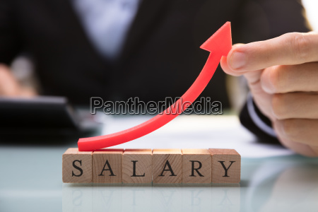 businessperson holding red arrow over salary