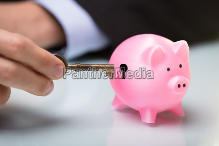 person inserting key in piggy banks
