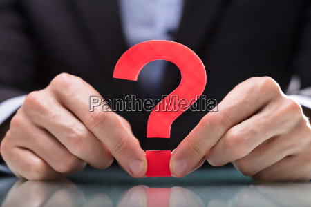 businessperson holding question mark sign