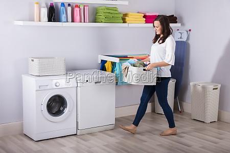woman standing near washing machine with