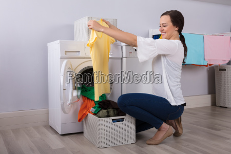woman looking at cleaned yellow tshirt