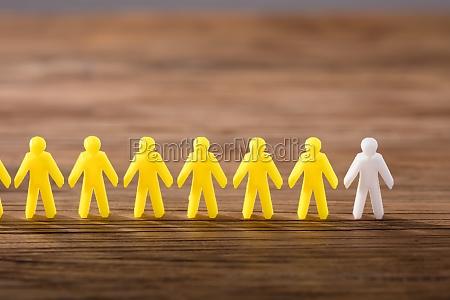 white figure standing among yellow human