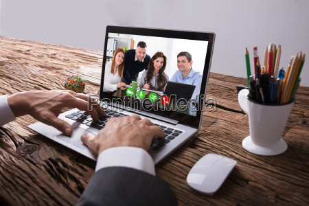 businessperson video conferencing with colleague on