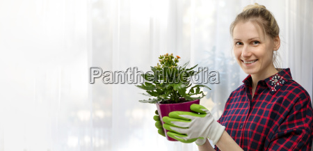 young smiling woman holding flowerpot in