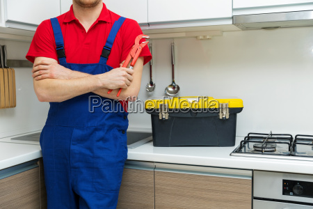 plumber with wrench in hand standing